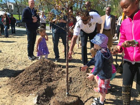 Crowd members help plant a crab apple tree in St. Cloud's