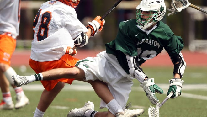 Delbarton's Keegan Khan is checked by Mountain Lakes DanOnorati after his shot on goal during their boys lacrosse matchup. The Green Wave won 8-3. April 30, 2016 Mountain Lakes, N.J.
