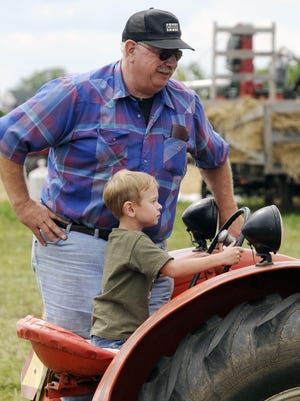 Cole Sprang of Manitowoc prepares to park a tractor with the help of his grandfather Roger Loose of Newton during the Mid-Lakes Rustic Iron Antique Tractor Show in 2008.