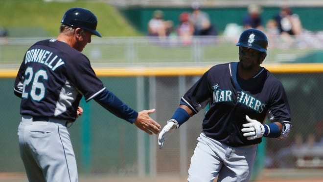 Seattle Mariners' Rickie Weeks, right, rounds the bases after hitting a home run as he shakes hands with third base coach Rich Donnelly (26) during the first inning of a spring training baseball game against the Cleveland Indians Tuesday, March 31, 2015, in Goodyear, Ariz.