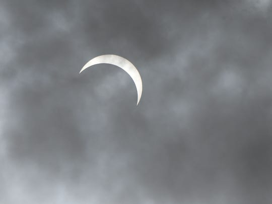 The moon passes in front of the sun during the eclipse Monday afternoon and clouds made it possible to photograph the lunar/solar event without special filters.