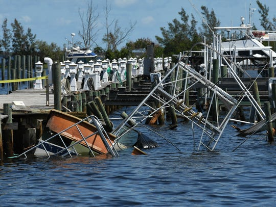 A capsized boat sits on the bottom ned to the dock