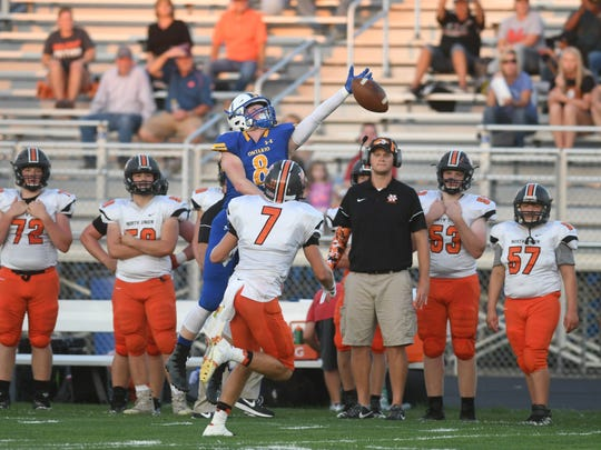 Ontario's Nolan Hatfield tries to haul in a pass over North Union's Chris Cox.