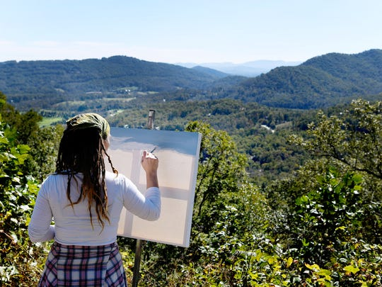 Lindsay Dunbar, of Asheville, works on a landscape painting along the Blue Ridge Parkway. The third week in October is the single busiest weekend on the parkway.