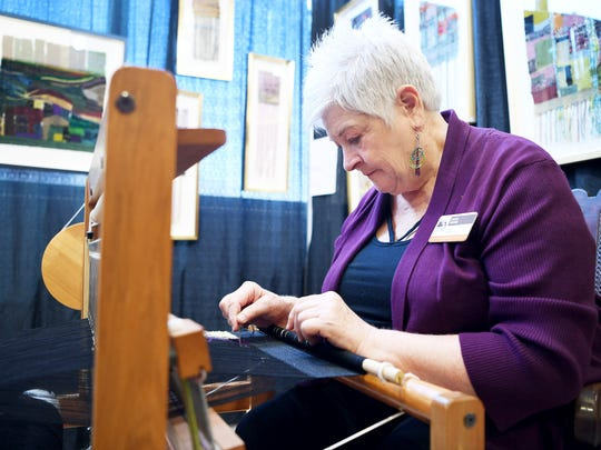 Betsy Meyer weaves at her booth at the Craft Fair of
