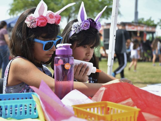 Sisters Jazmin Mora, 8, and Violeta Mora, 7, enjoy the arts and crafts table at Visalia Parks and Recreation's Eggstravaganza event on Saturday, March 31.