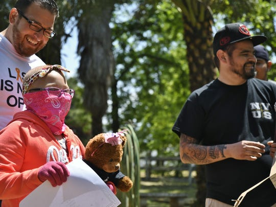 Members of NVUS car club gives Amanda Aceves a teddy bear. The 8-year-old girl was diagnosed with Leukemia in February.