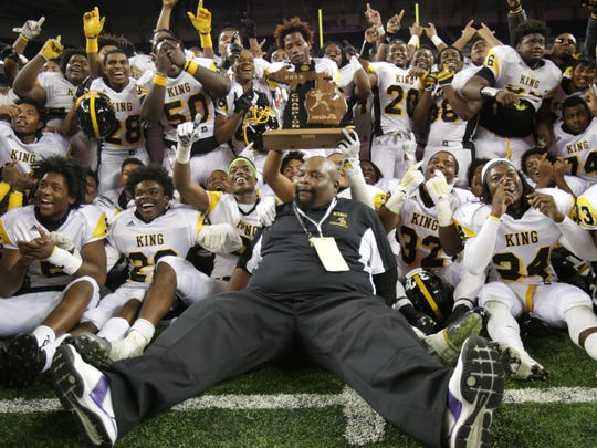 Detroit Martin Luther King head coach Dale Harvel sits on the ground for a team picture after defeating Lowell, 40-38, during the Michigan High School Athletic Association football finals at Ford Field in Detroit on Friday, Nov. 27, 2015.