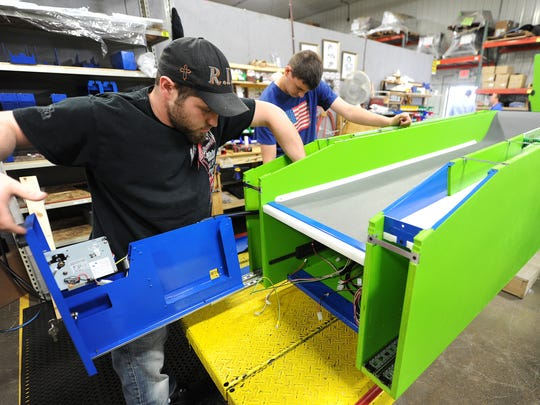 Assemblers Bo White and Joe Stachura build a Skee-Ball machine in the assembly area at Bay Tek Games in Pulaski.