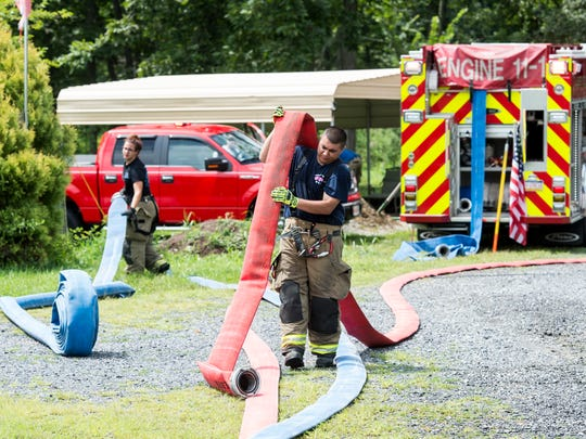 Firefighters roll up hoses after containing a residential fire in the 2900 block of Stoney Point Road in Reading Township on Tuesday, August 8, 2017.