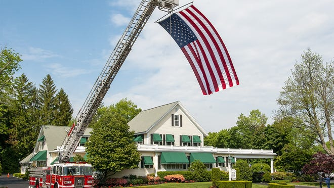 A large American flag flies from the Rutland Fire Department ladder truck outside Miles Funeral Home Wednesday for the wake of Rutland Police Officer John D. Songy. He died Friday after being stricken with COVID-19 more than a month earlier. Songy, 48, a detective, had been a member of the Rutland Police Department for eight years.