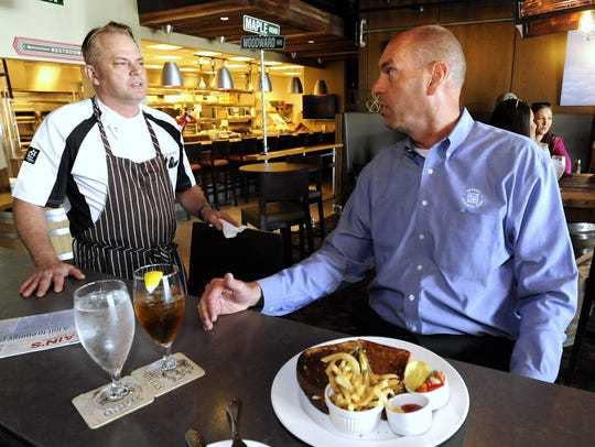 The Stand chef and owner Paul Grosz, left, talks with
