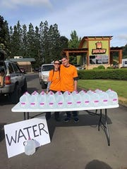 Adam Wilhite and Shawna Hermans bought 126 gallons of water in Lebanon and drove them to Salem to give to families in need for free on Wednesday, May 30, 2018.