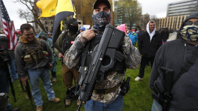 In this April 30, 2020, file photo, a protester carries his rifle at the State Capitol in Lansing.