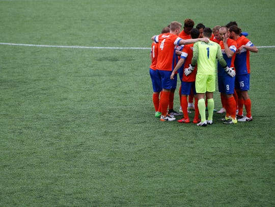 The FC Cincinnati starting eleven huddle just before