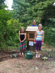 """Members of Girl Scout Troop No. 7019 donated and erected a little library at the Monk Botanical Gardens during the gardens' """"StoryWalk"""" event on July 9. The library is located near the treehouse, and is mounted at a low level on a tree stump, designed for young readers. The girls from the troop are sponsoring the library, and also planted hostas around the base. Brad Schmicker guided the gardens' Teen Garden Club and the girl scout troop in the construction of the library. The girl scout troop, which is led by Bobbi Flemming, will maintain the book supply, and will hold a book drive in the future. Pictured here with the finished library are Scouts Isabelle Radant, at left, Hailey Radant, center, and Emma Kutella, at right."""