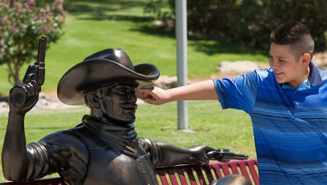 Luis Torres, 11, moves slowly to poke the new bronze Pistol Pete statue, saying after words he thought it was a living statue, a person in make up, Wednesday July 25, 2018 at New Mexico State University. The new bronze statue was inspired by a similar mascot statue at Texas Christian Universityin Fort Worth, Texas. the statue is modeled on Pistol Pete sudent mascot Caleb Gustin. Being placed outside of Corbett Center, NMSU officials hope students and visitors will stop by and take pictures with the sculpture.
