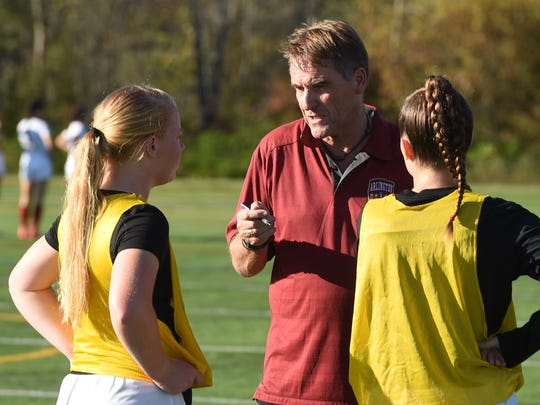 Kieran McIlvenny, center, head coach of Arlington's girls soccer team, talks with players Kayla Napier, left, and Megan MacDonald, right, before a game against Somers on Oct. 10, 2017.