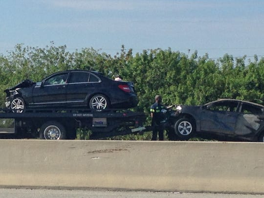 Two vehicles are removed from the scene of a fatal crash on I-95 Sunday