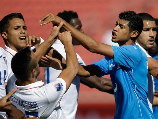 United States forward Jerome Kiesewetter, left, falls after being pushed by Honduras defender Marcelo Pereira, right, during a tussle between teams in the second half of a CONCACAF men's Olympics semifinal qualifying soccer match, Saturday, Oct. 10, 2015, in Sandy, Utah. Honduras won 2-0. (AP Photo/Rick Bowmer)