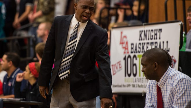 St. Martinville Coach Darrel Mitchell Sr. speaks to players on the bench during the first quarter of an LHSAA basketball game at Lafayette Christian Academy in Lafayette, La., Tuesday, Dec. 1, 2015.