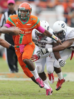 Damien Fleming picks up some yards for FAMU while truing to escape Howard's defenders in last year's homecoming game at Bragg Stadium.