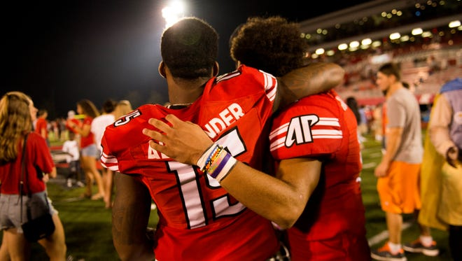 Austin Peay's Josh Alexander holds his teammate, DeAngelo Wilson, as they walk down the field filled with fans following their win against Morehead State on Sept 16, 2017.