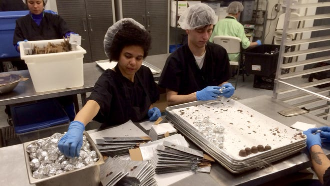 Workers at the Dixie Elixirs edible marijuana bakery in Denver hand-wrap pot-infused chocolate truffles on March 20.