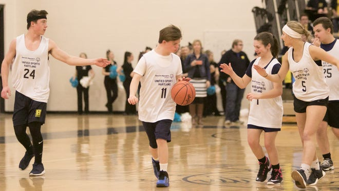 Jamison Kohli, center, brings the ball down court, supported by Hartland teammates from left, Jacob Behnke, Jaimie Flores, Amanda Maga and Noah Thomas in a Unified Sports basketball game Thursday, Jan. 25, 2018. Unified Sports is a Special Olympics program.