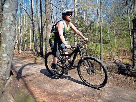 A mountain cyclist rides down a trail at the Bent Creek