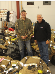 Ray Ahonen (l) and Denny Hughes with some of the collected fire gear.