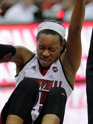 Louisville's Asia Durr grimaces after hitting the court hard during play.