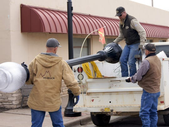 Gila Valley Electric employees take one of the lightposts down Tuesday afternoon to get it installed in downtown Silver City.