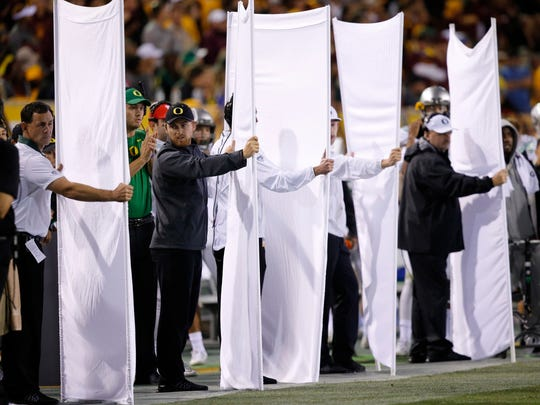 Oregon football team staff use sheets to block the
