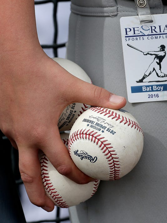 A bat boy holds game balls before a spring training baseball game between the Seattle Mariners and the Arizona Diamondbacks Monday, March 7, 2016, in Peoria, Ariz. (AP Photo/Charlie Riedel)