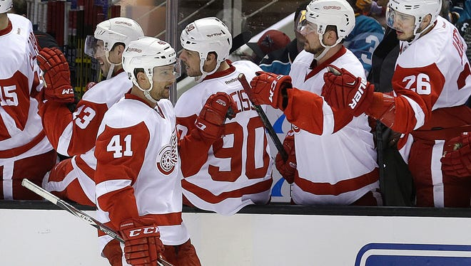 Red Wings forward Luke Glendening (41) celebrates with teammates after scoring the winning goal against the Sharks during the third period Thursday night.