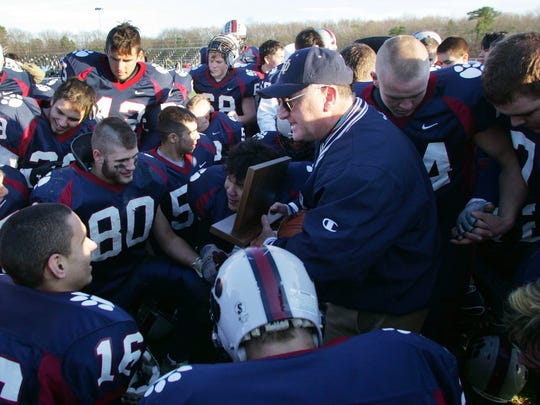 Lou Vircillo talks to his team holding the state championship trophy in 2006.