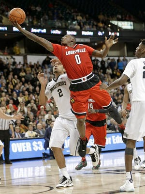 Louisville's Terry Rozier (0) drives between Wake Forest's Cornelius Hudson (25) and Devin Thomas (2) during the second half of an NCAA college basketball game in Charlotte, N.C., Sunday, Jan. 4, 2015. Louisville won 85-76. (AP Photo/Chuck Burton)