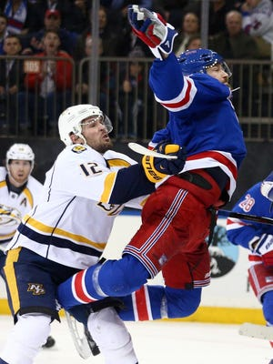 Rangers defenseman Kevin Klein is pushed from behind by Predators center Mike Fisher during the third period.