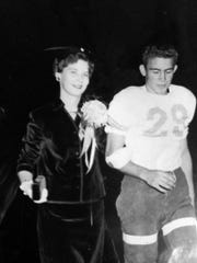 Freddie Ussery walks with a maid of the homecoming court on the field during a halftime ceremony of a Bolton football game when he was a senior defensive back for the Bears in the fall of 1955.