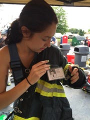 Kay Low, 20, of Vineland, pins a photo of a fallen