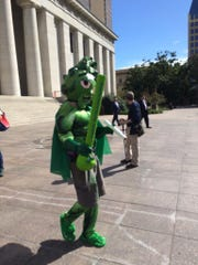 A parody of ResponsibleOhio's mascot, Buddie, was protesting a new research facility announced Tuesday.