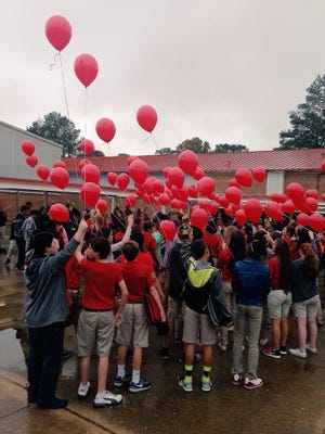 Pineville Junior High students prepare to release red balloons as part of their Red Ribbon Week kickoff Monday.