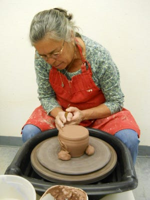 Karen Miskimins shapes a jar as she learns how to use the potters wheel.