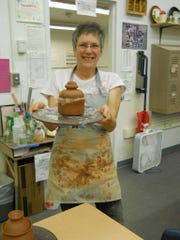 Janet Reynolds shows off her pottery.