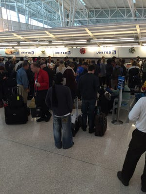 A long line of passengers wait at the United ticket counter on Tuesday.