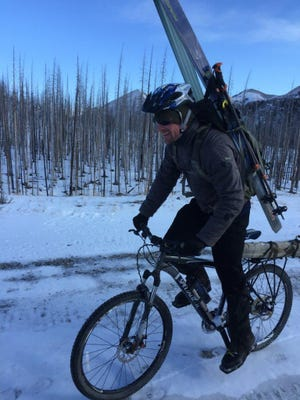 With skis on his back, Nate Emer rides a mountain bike on the North Fork Teton Road on a snow survey trip on the North Fork of the Teton River.