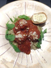 Grass-fed beef meatballs with tomato and red pepper sauce, arugula and quinoa. By Amber Solnick, private chef and consultant.