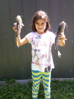 Carole Currie, 8, shows her two catfish haul at Lake Julian. She and her brother, Walter, compete each year in the Lake Julian Kids Fishing Tournament.