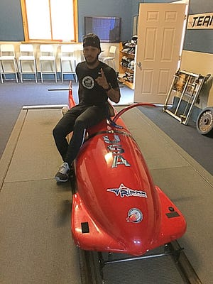 Jovan Wilkins poses on a bobsled at the Olympic Center in Lake Placid.